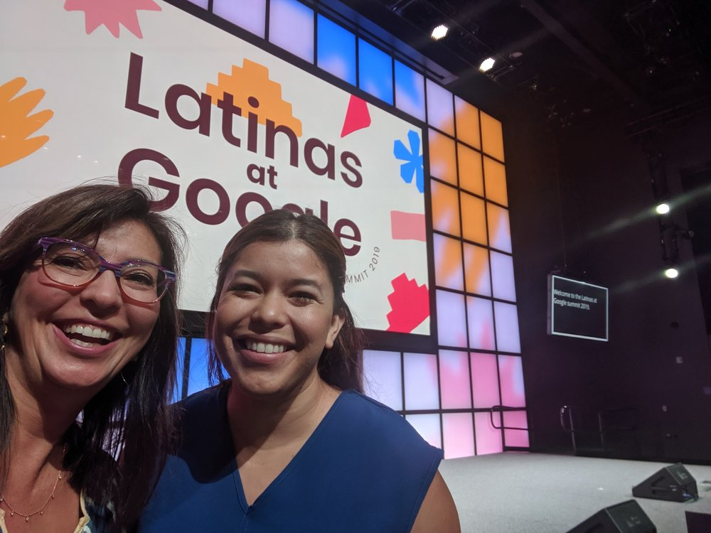 """Two people, Monica and fellow Googler Rosie Giddeon, are smiling at the camera. In the background is a stage with a slide that says """"Latinas at Google""""."""