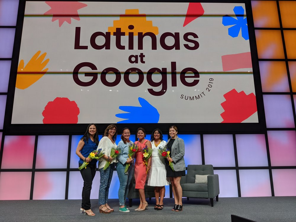 """Monica and five others on stage under a """"Latinas at Google"""" sign. They are smiling at the camera and holding bouquets of colorful flowers."""