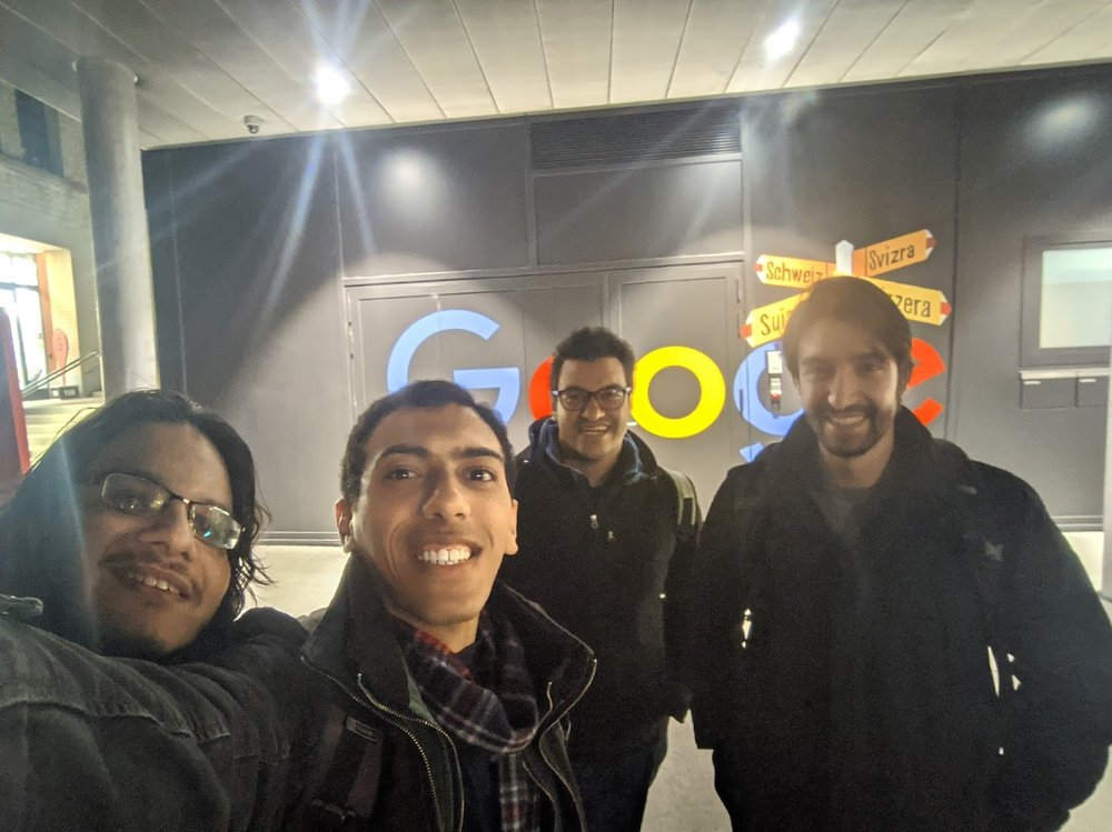 Yosri and three other new Googlers stand in front of a Google sign.