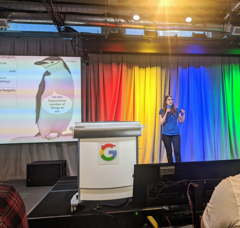 Avital speaking next to a podium with a Google logo and a slide with a penguin on it.