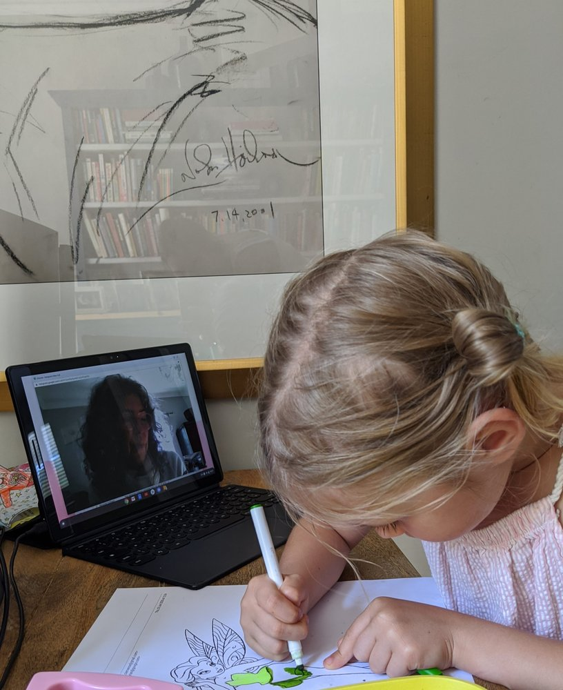 photo of a girl coloring while having a virtual video call with her grandma on a laptop