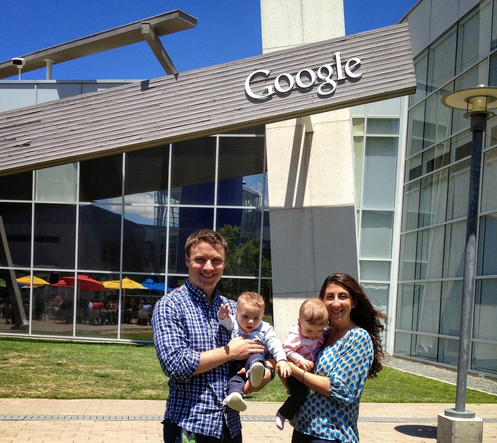 Dennis and his wife, Tiffany, standing and smiling in front of a Google building, while holding their twins, Gabriella and Mason