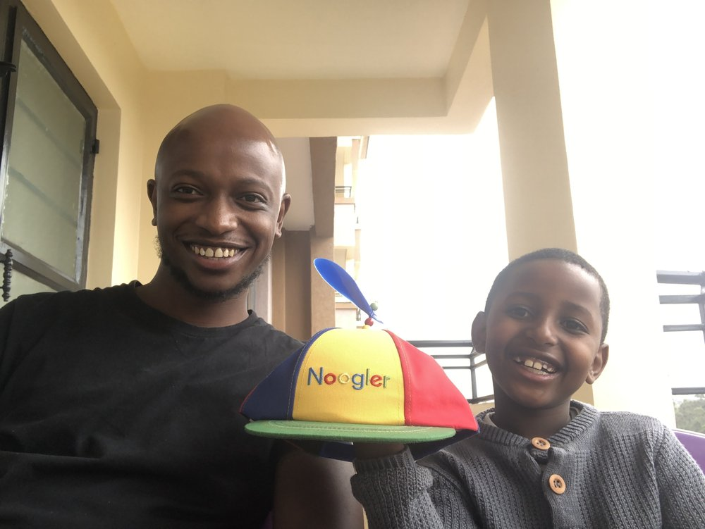 Andrew and his son smile at the camera holding a Noogler hat.