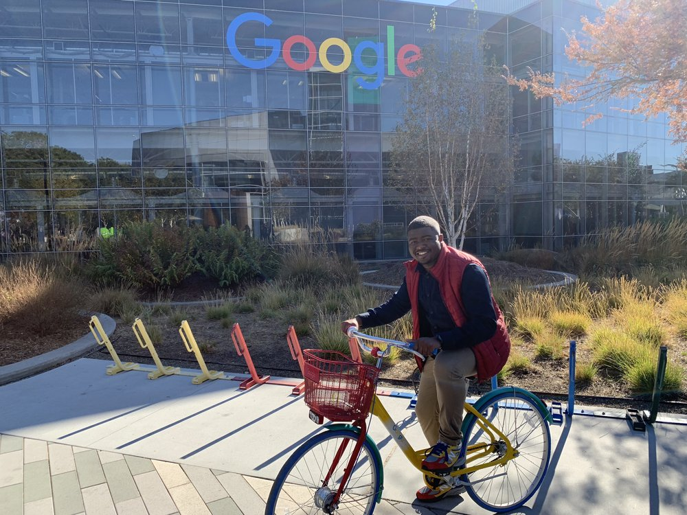 "Rob outdoors on a red, yellow, blue, and green ""Google bike"" in front of the large Google sign at Google headquarters in Mountain View, California."