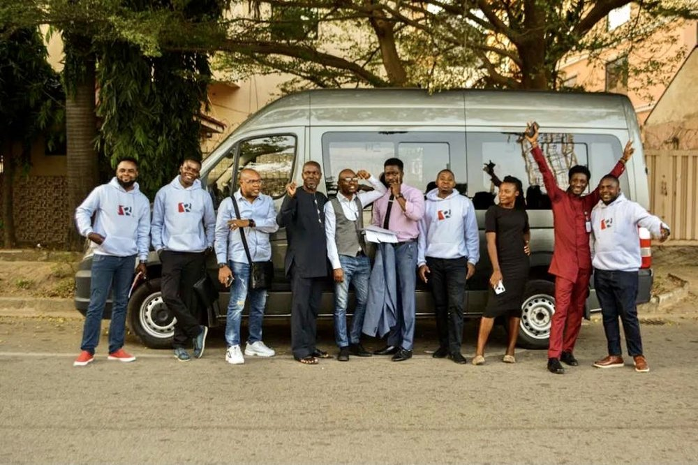 The Ripples Nigeria team stand in front of a minivan smiling to the camera in corporate jumpers and work attire.
