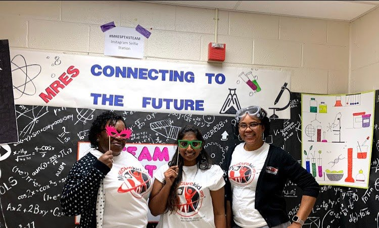 "Image of three women in front of a sign that says, ""Connecting to the future""."