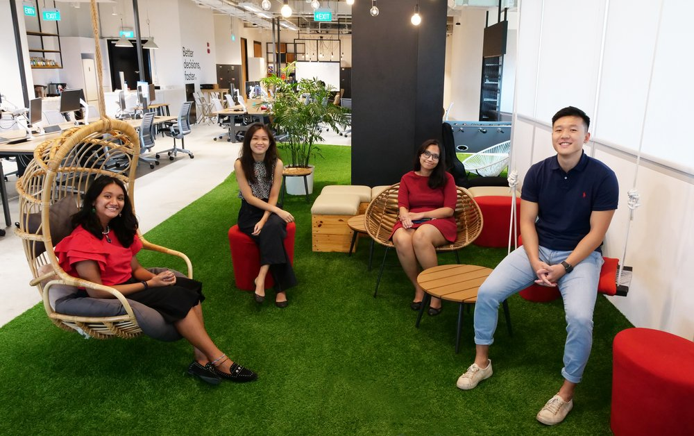 An image of Skills Ignition trainee Gaviota with three of her fellow trainers, two women, one man, in the offices of Omnicom Media Group — their host company. They're sitting on seats in a casual area with astroturf on the floor.