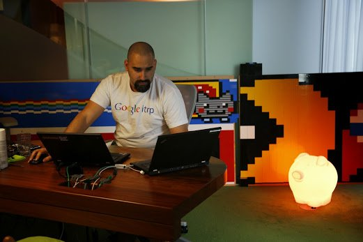 """Jesus working at a desk wearing a """"Google ITRP"""" shirt. A light and large pacman made of legos are next to him."""