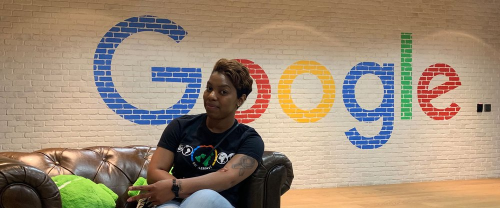 Joy sits on a brown couch. Behind her is the Google logo painted on a white brick wall.