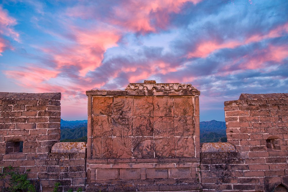 A section of the great wall with a Kirin motif, showing a mythical Chinese creature, against a backdrop of pink and blue clouds.