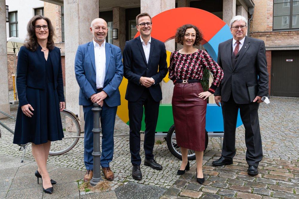 Auf dem Bild sieht man fünf Personen, die vor dem Google Büro in Berlin stehen.