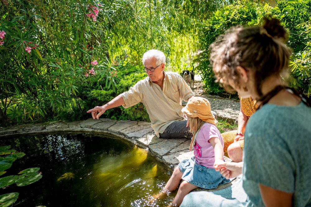 A man sits with a woman and a young child at French cottage Les Courtines, pointing towards a pond.