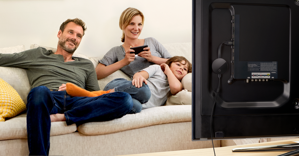 A family (two parents and a child) on a couch watching TV