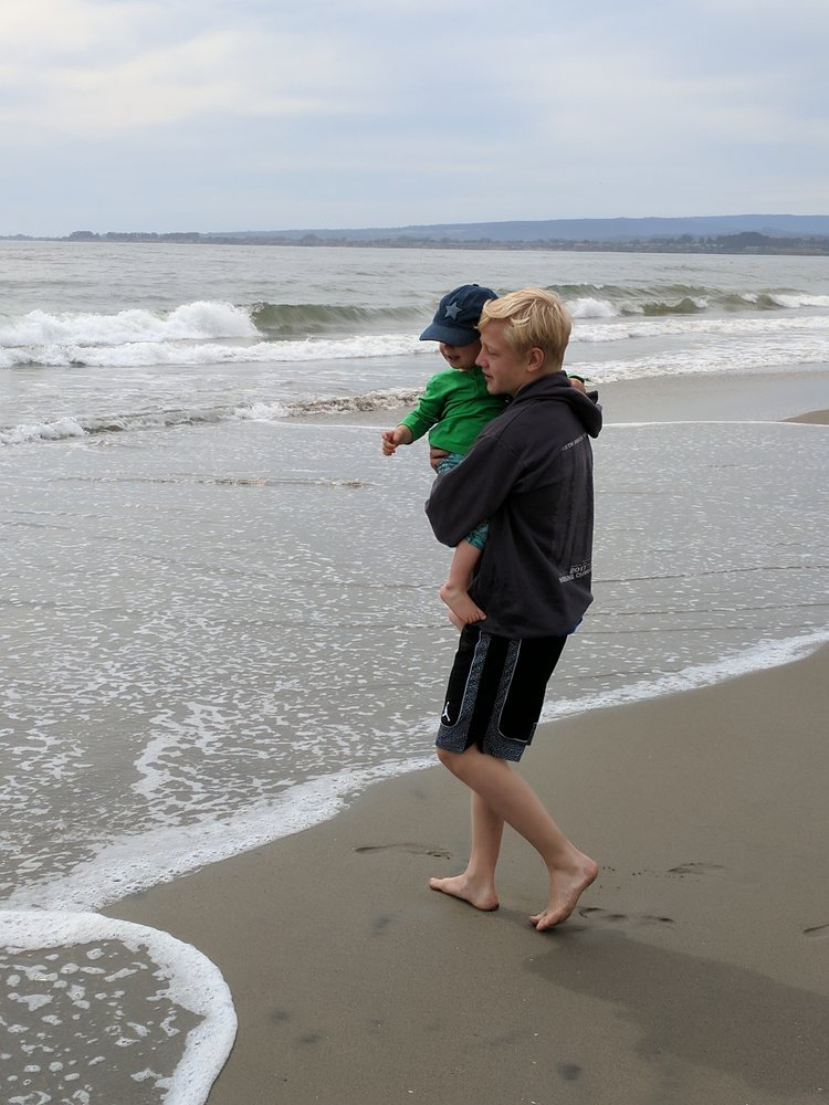 An older brother holds a younger brother while walking on the beach.