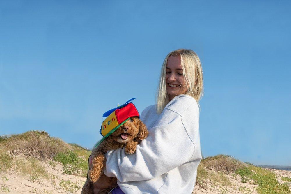 Livia Seibert holding her dog that's wearing a Google intern hat.