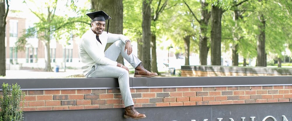 Dre' wears a graduation cap while sitting on a wall, with trees and buildings in the background.