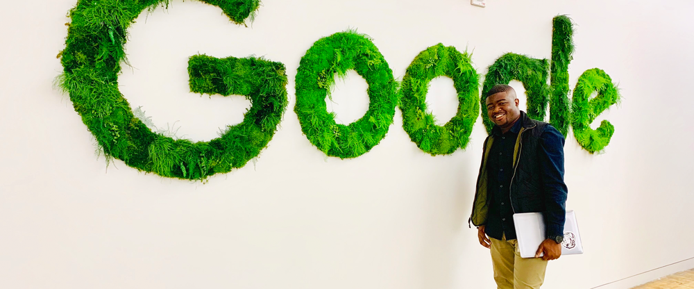 """Rob holding a laptop and standing next to white wall with large sign made of grass and moss that spells out the word, """"Google."""""""