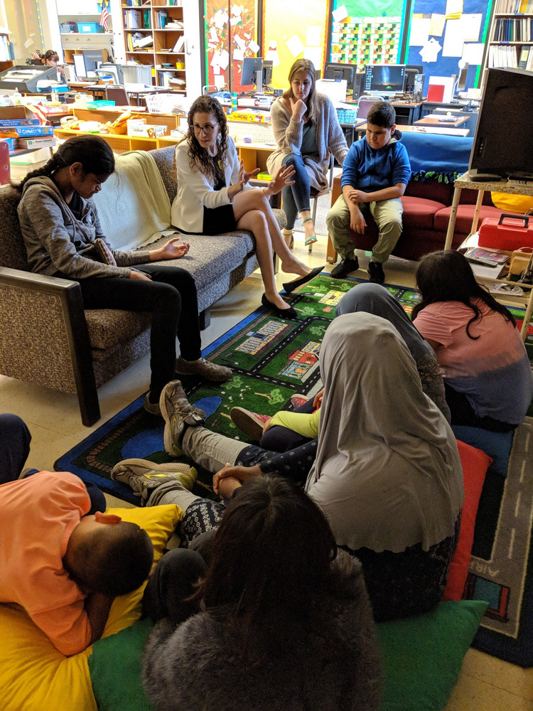 Photo of Laura talking with young students in a classroom at the California School for the Blind