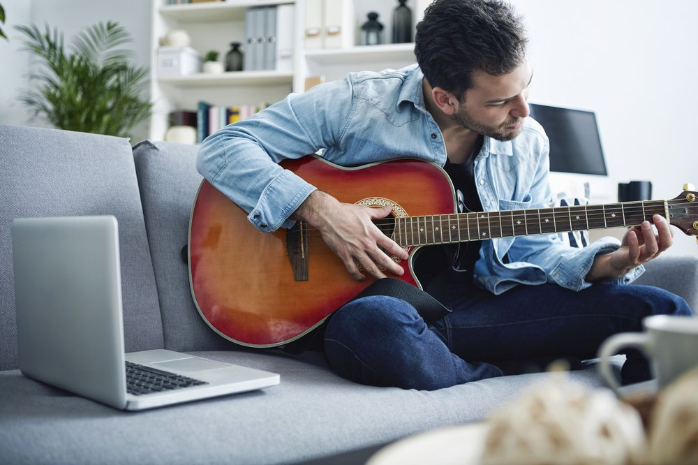 Man playing guitar on gray sofa