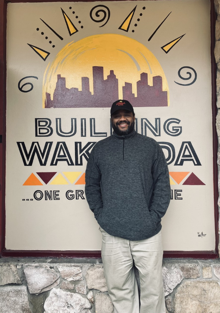 Image of Marcus Davis, owner of The Breakfast Klub, standing in front of a mural.
