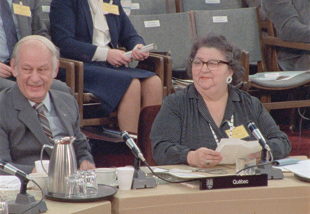 Mary Two-Axe Earley sits next to former Premier Rene Levesque at a desk with microphones on it.