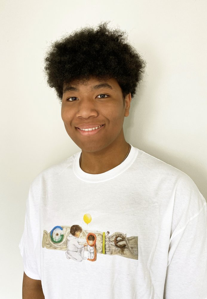 Photo of a young man looking into the camera and smiling.