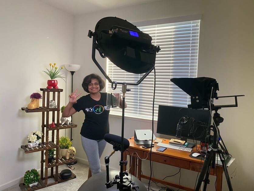 Priyanka in her work-from-home studio, which includes a lighting and camera setup, desk and display shelf of potted plants.