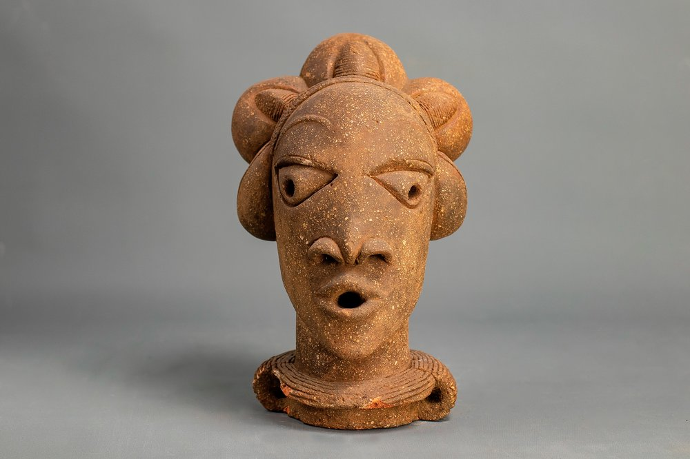 Image depicts a stylised sculpture of a female head. This figure has triangular eyes with holes in its eyes and mouth and hair parted into mounds. The sculpture is created in a light brown material with flecks of white .
