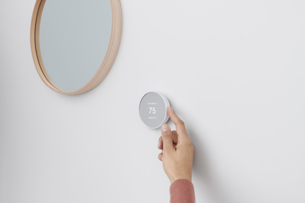 Image showing a hand adjusting a Nest Thermostat on a wall next to a circular mirror.