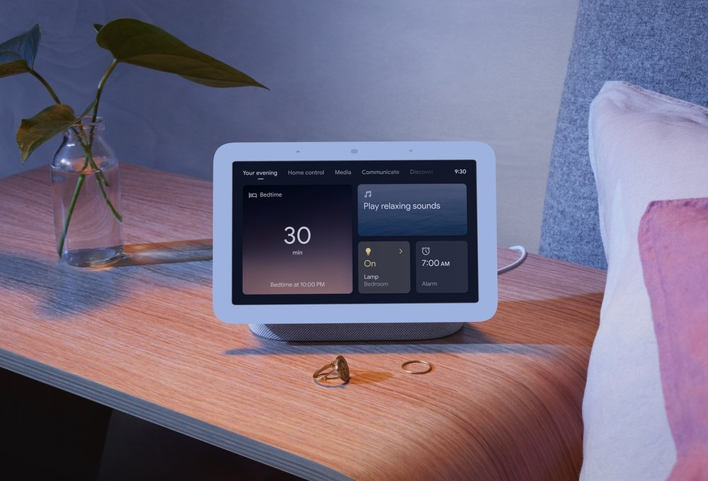 Image showing a Nest Hub on a bedside table with the Your Evening page on the screen.