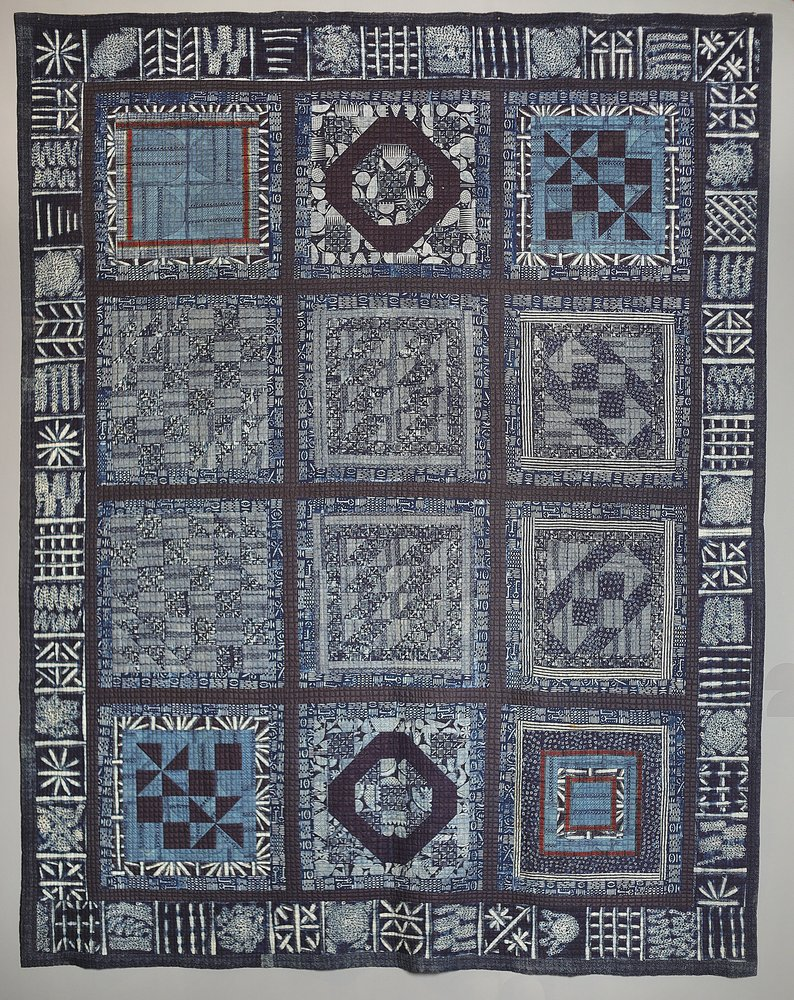 This image shows a  work comprised of sections of different fabrics which have been joined together to form a patchwork wall hanging. Indigo is the predominant color of this work, but white black and light blue are also present Each piece of cloth has geometric shapes woven into it.
