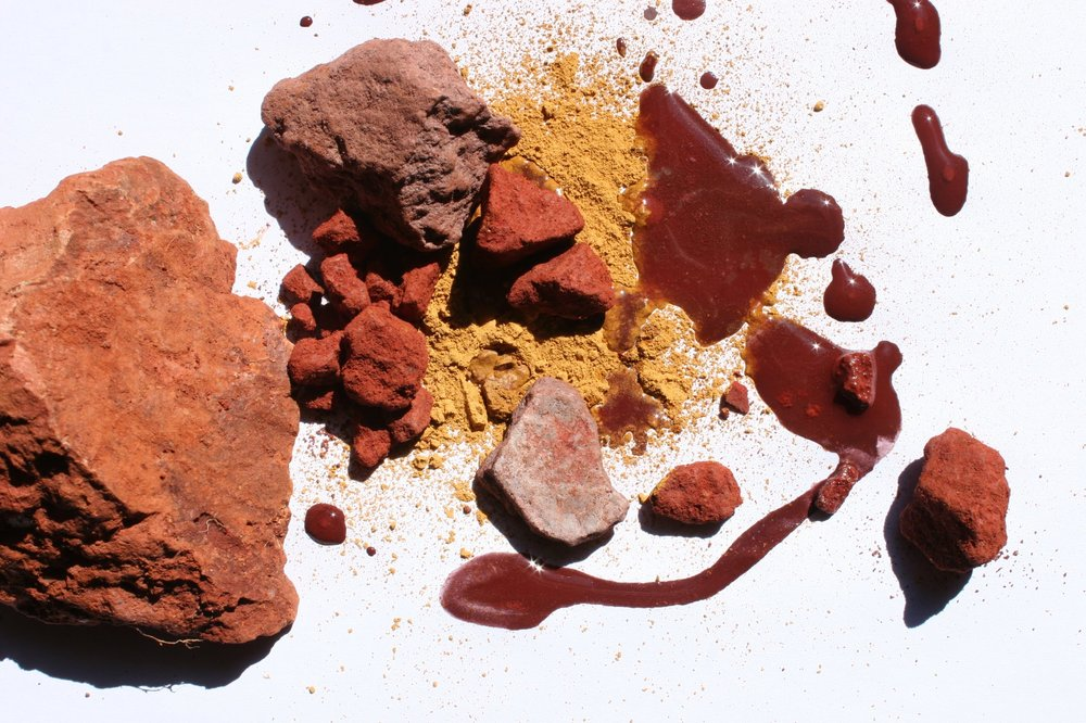 Image of ochre in various forms: as a rock, as powder and as liquid. Image is in hues of red, yellow and brown.