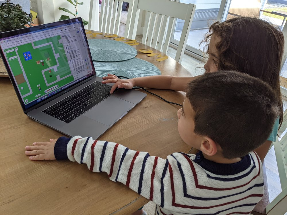 Two children sitting at a dining room table looking at an open laptop that shows the I/O Adventure game on the screen.