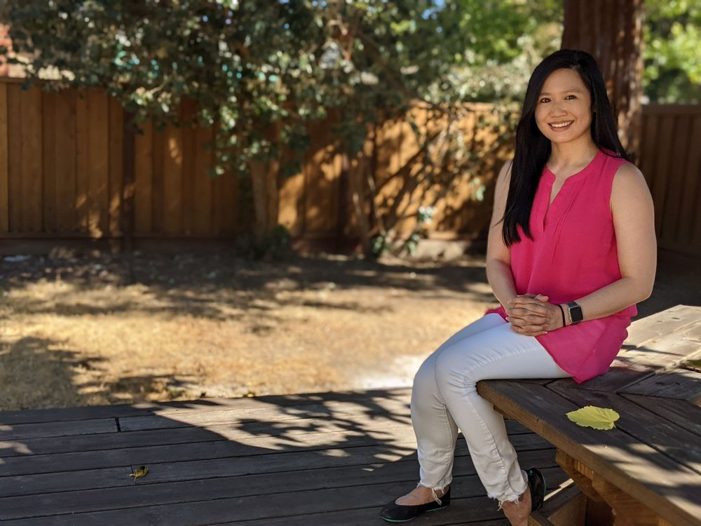 A photo of Alicia Chang sitting on a bench outside. She is looking into the camera and smiling.
