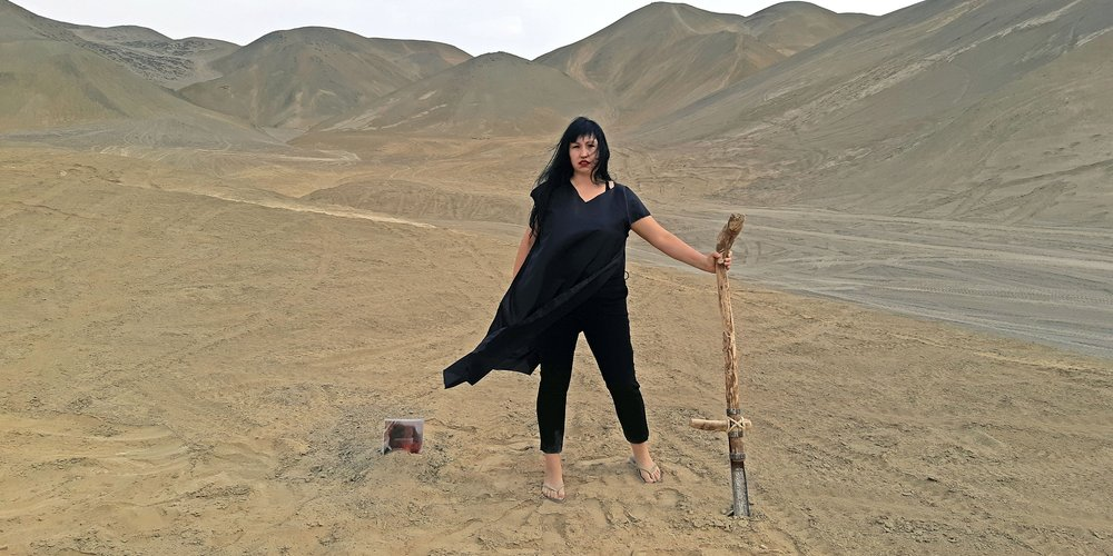 A woman in a desert holding a staff
