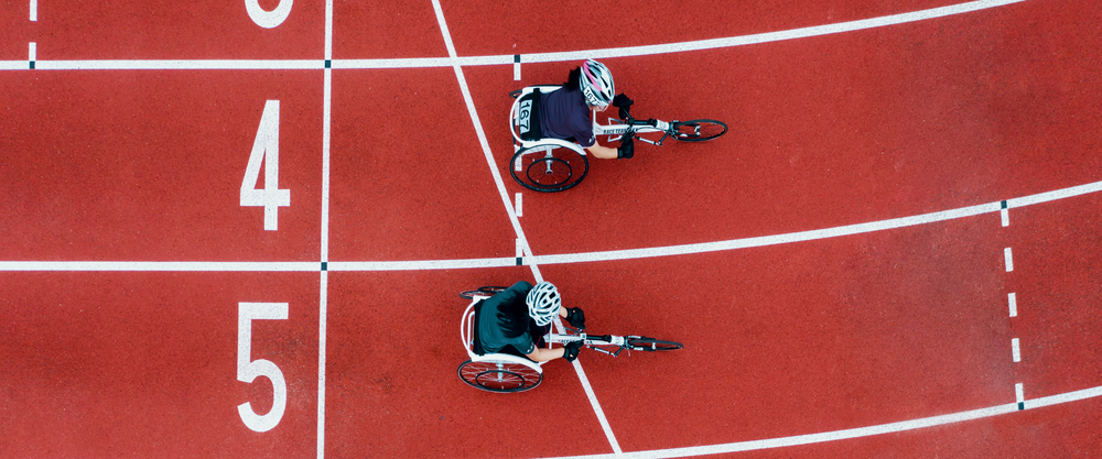 Overhead photograph of a track with two wheelchair paralympians racing.