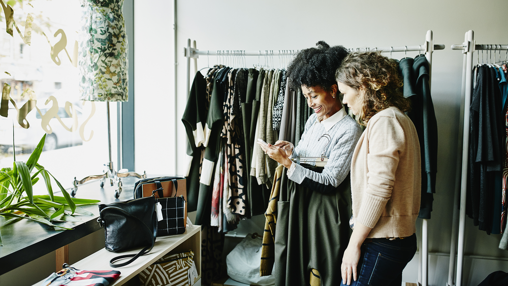 A photograph of two people shopping at a clothing store.