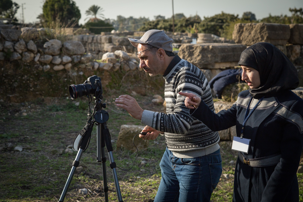 Two people standing behind a camera at the Temple of Eshmun.