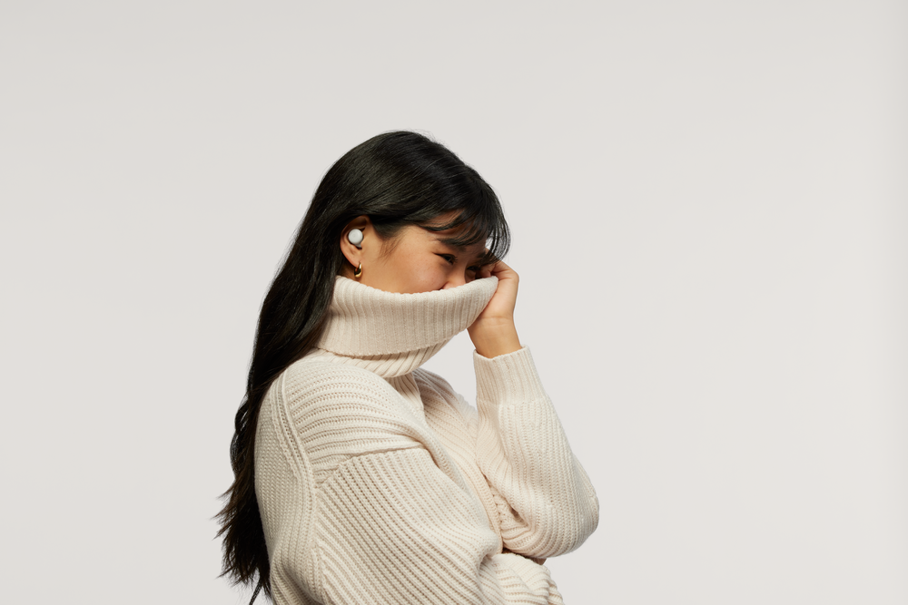 Image showing a person wearing a large white turtleneck with half of their face hidden inside the turtleneck. There are white Pixel Buds in the person's ears.