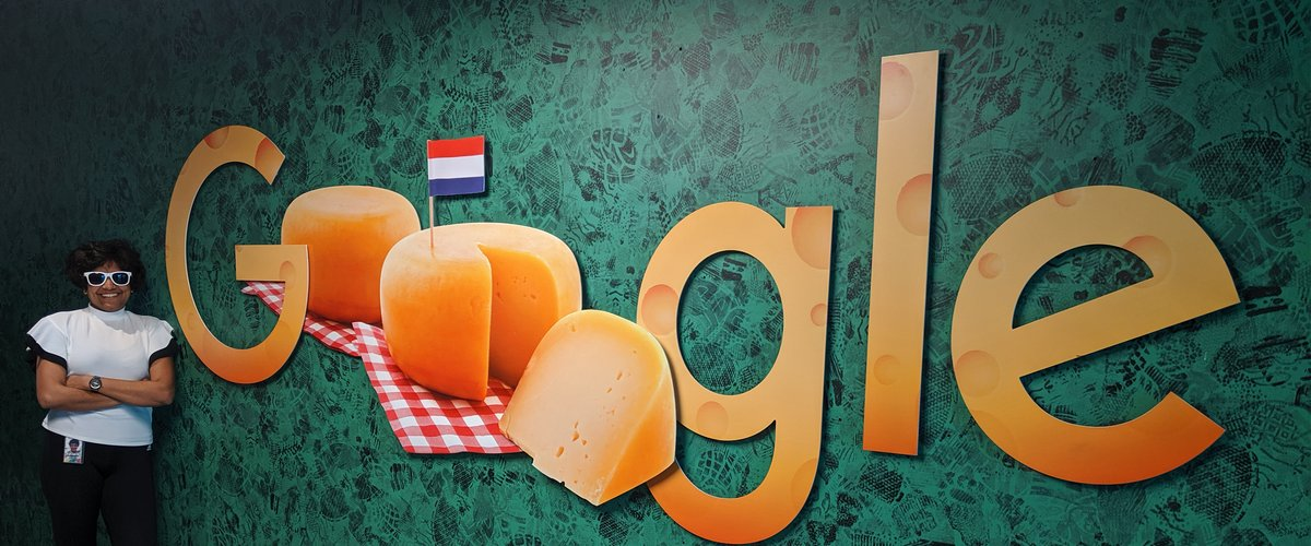 Priyanka stands by a cheese-themed Google logo at the Amsterdam office.jpg
