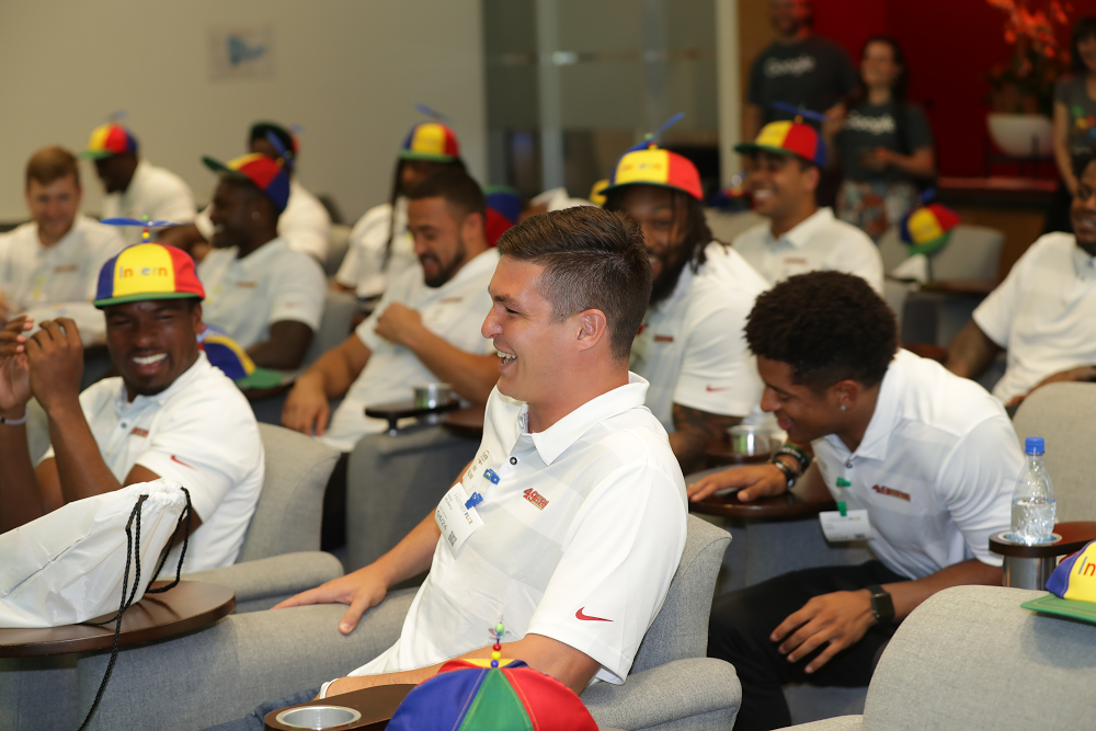 Members of the San Francisco 49ers sitting in chairs wearing intern hats and laughing.