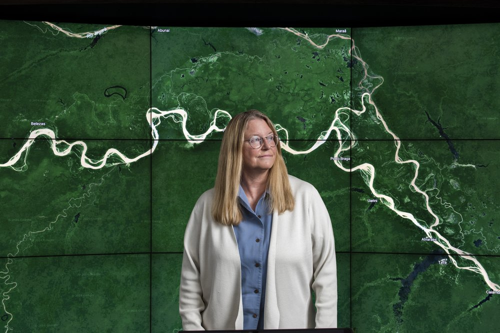 Image of Rebecca Moore in a white cardigan standing in front of a satellite map image.