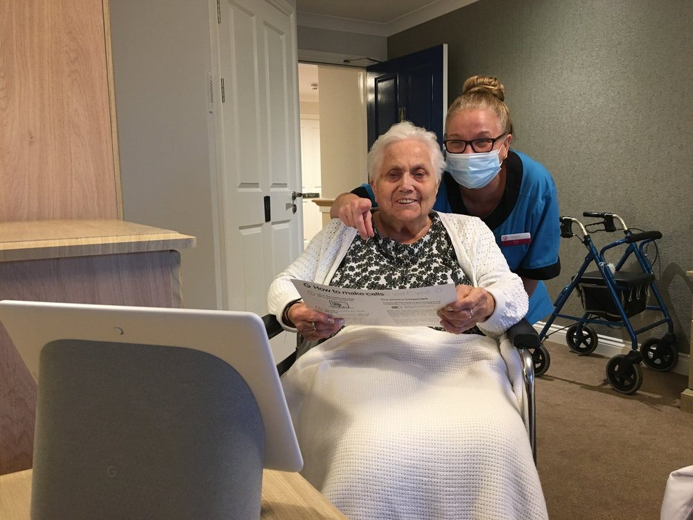 Image shows an elderly woman in a wheelchair with a nurse who is wearing a mask leaning over her shoulder. Bother women are looking at a Google Nest Hub Max and reading a booklet with instructions. The nurse is pointing at the screen, and the woman in the wheelchair is smiling.
