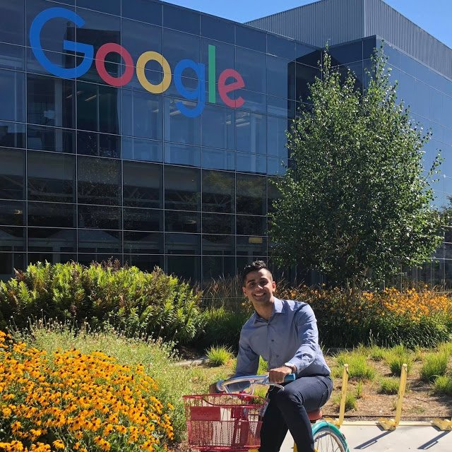 Reza outside on a Google bike in from of the Google sign at headquarters.