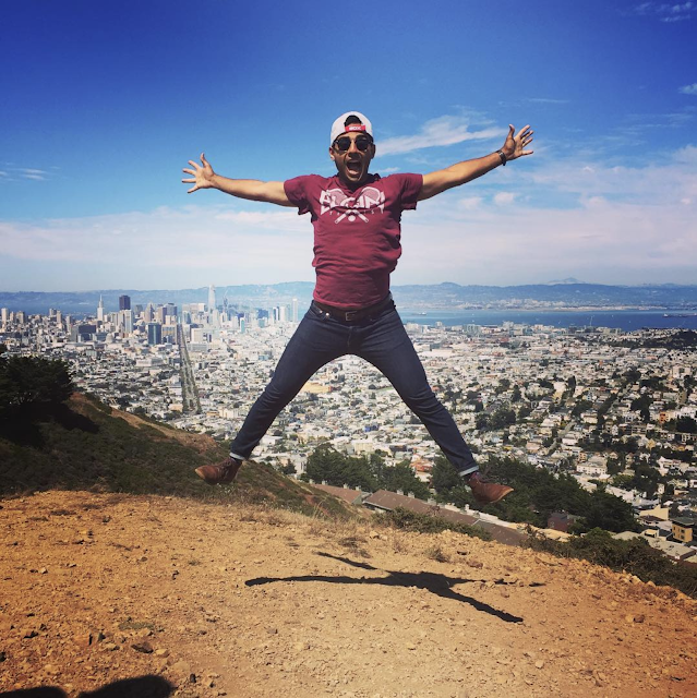 Reza jumping outdoors with a city behind him