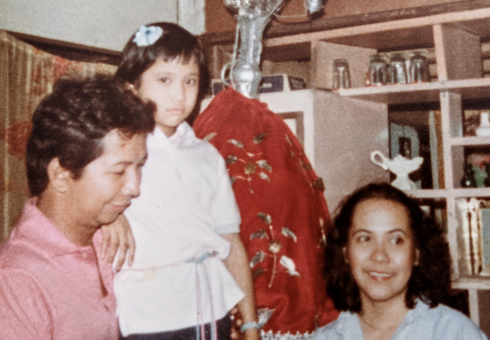 Three people, two adults and one child, are in an old photograph. The child is wearing a white shirt and a white hair pin and looking into the camera. She is leaning on an adult man who is wearing a pink shirt, looking down and smiling. To the left of the child is a woman with dark curly hair, who is looking away from the camera and smiling.