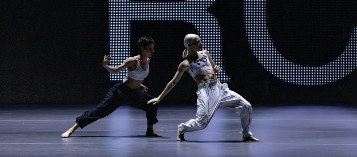 Two dancers performing on a stage.png