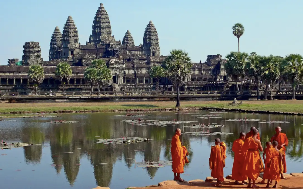 An Image of the Angkor Wat with a groups of monks wearing orange tunics