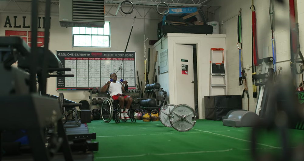 Garrison Redd, a male individual who uses a wheelchair, pulls a strength band from the ceiling of a gym. He is surrounded by various athletic weights and equipment.