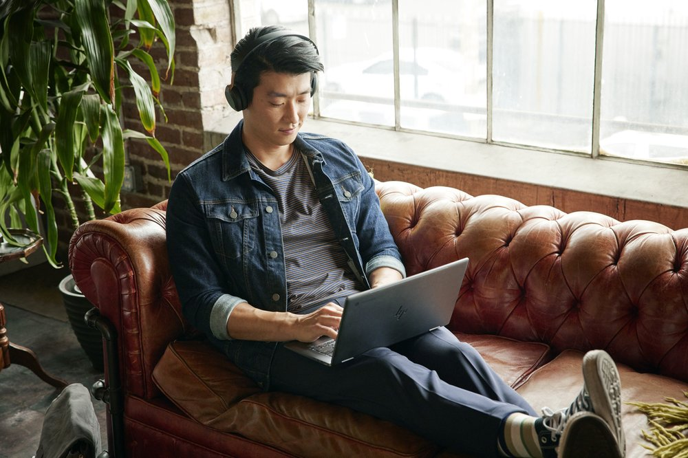 A man wearing over ear headphones sits cross legged on a brown leather couch, while working on a Chromebook laptop in his lap.
